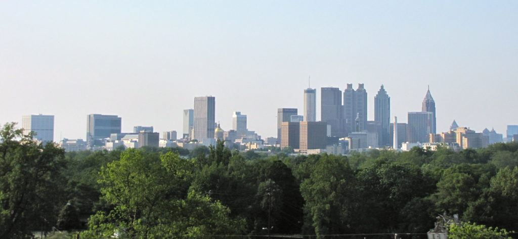 An image of Atlanta's downtown skyline with trees in the foreground.